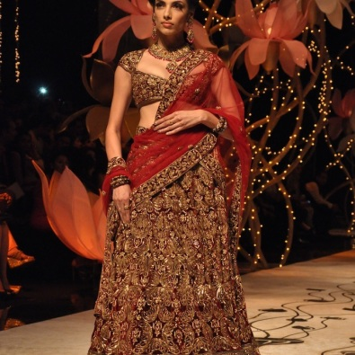 A red bridal lehenga heavily embellished with gold