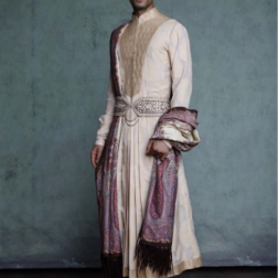 A crème, pleated silk brocade kurta with a beige brocade yoke and borders, worn with a churidar. Accessorised with a traditional Jamewar shawl and jewel belt.