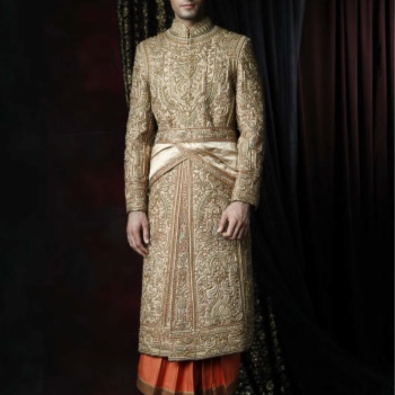 A brocade base sherwani with heavy antique gold gota embroidery, worn with a long, pleated rust kurta and churidar. Ensemble ornamented with a draped, embroidered kamarbandh and embroidered juttis.