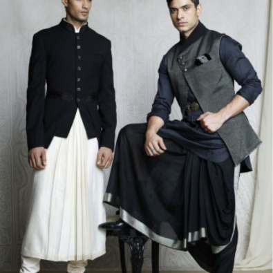 A black, crepe wool bandhgala with embroidered velvet collar and waist belt, adorned with mother of pearl jewel buttons. Worn with a long crème, pleated kurta and churidar. A black handloom, open front Nehru jacket with jersey draped collar and back. Paired with a black kurti and draped dhoti with brocade borders.