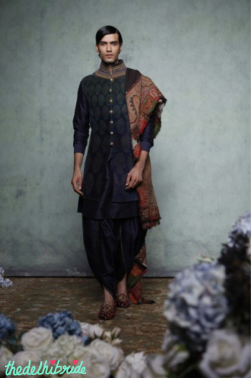 Ombre dyed, sleeveless velvet sherwani in shades of green and blue, with ornate etched print, antique zardozi embroidered collar and jewel buttons. Paired with a royal blue kurta and salwar, along with a traditional Jamewar shawl.