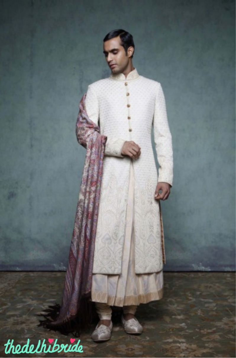 A light gold sherwani with traditional chikankari, and resham and kasab embroidery on the borders. Worn with a long, pleated, silk brocade kurta and churidar. Look enhanced by a Jamewar shawl, embroidered juttis and jewel buttons on the sherwani.