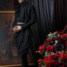 A black crepe, wool bandhgala with jersey drape and sleeves. Paired with a crepe, wool draped trouser and shirt. Look enhanced with a jewel belt.