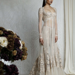 A champagne gold, embroidered bustier adorned with 3D sheer silk flowers and Swarovski Elements, worn with embroidered sheer net pants and a sensuous sheer net jacket embellished with resham, appliqué, 3D sheer silk flowers, tulle frill and Swarovski Elements