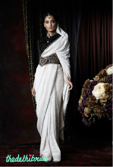An ivory chiffon sari with traditional chikankari and mukaish-highlighted chikankari border. Worn with an open mandarin velveteen blouse with antique zardozi highlights on the collar. Ensemble enhanced with antique zardozi corset belt.
