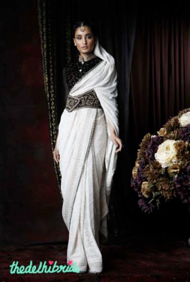 An ivory chiffon sari with traditional chikankari and mukaish-highlighted chikankari border. Worn with an open mandarin velveteen blouse with antique zardozi highlights on the collar. Ensemble enhanced with antique zardozi corset belt.