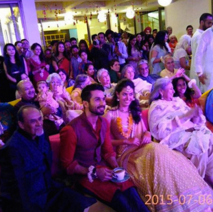 The couple sitting with the guests at the Sangeet