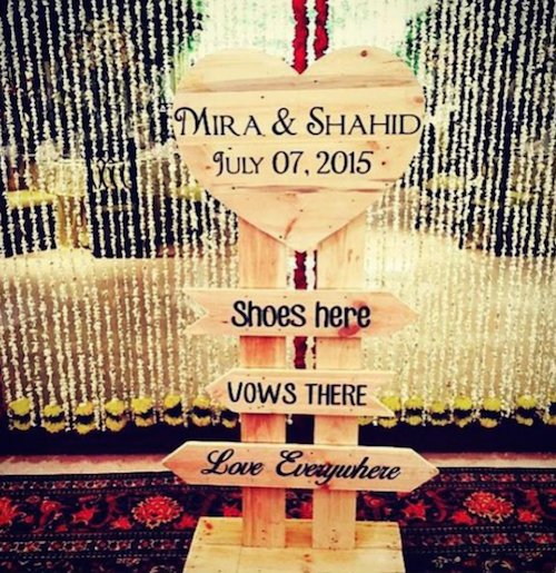 Shahid Kapoor Mira Rajput wedding cute wooden signboard at entry with white and yellow flowers backdrop shoes here vows there love everywhere