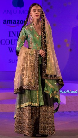 Green jacket embroidered with gold floral applique work, paired with a black lehenga