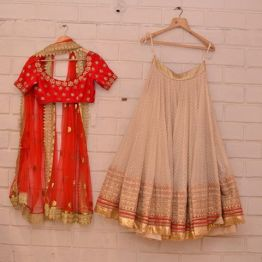 Heavily embroidered red blouse with ivory lehenga