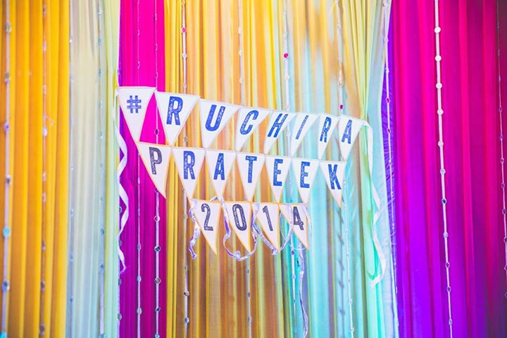 Wedding decor - backdrop idea - colourful fabric with bride & groom names on banner